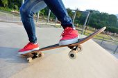 foto of skateboarding  - young skateboarder legs skateboarding at skatepark ramp - JPG