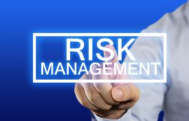 stock photo of risk  - Business concept image of a businessman clicking Risk Management button on virtual screen over blue background - JPG