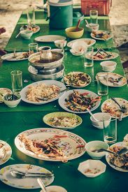 stock photo of table manners  - Remaining plates leftover on the table with remaining Thai food in vintage color - JPG