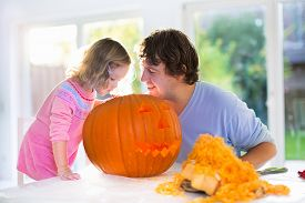 stock photo of carving  - Family carving pumpkin at Halloween - JPG