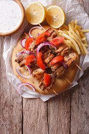 stock photo of souvlaki  - Greek souvlaki kebabs with vegetables and french fries on pita bread on the table - JPG