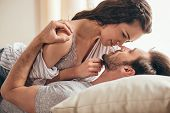 Close-up Portrait Of Beautiful Sensual Young Couple Hugging While Lying On Bed And Looking At Each O poster