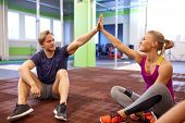 fitness, sport, exercising, gesture and people concept - happy couple resting and making high five i poster