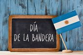 the text Dia de la Bandera, Flag Day written in Spanish in a chalkboard, and a flag of Argentina, on poster