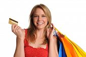 Young Girl holding shopping bags and credit card isolated on white