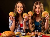 Hamburger fast food with ham and group people. Good Fast food concept. Friends two women eating sand poster