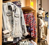 Shorts, Shirts, T-shirts And Jacket On The Store Shelf. Fashionable Clothes On The Shelves In The St poster