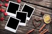 Four blank instant photo frames with small heart shapes and cinnamon on old wooden background.