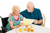 Disabled senior woman and her husband go over their medical and prescription drug bills.  Isolated o