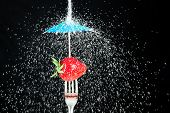 Healthy eating concept.  Strawberry on fork, protected from a stream of falling sugar by a cocktail umbrella.  Black background.