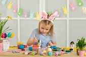 Little Child Girl With Easter Bunny Ears Painting Easter Eggs At Home. Adorable Child Prepare For Ea poster