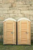 stock photo of porta-potties  - Portable toilets against stone wall subtle cross - JPG