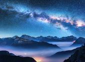 Milky Way Above Mountains In Fog At Night In Summer. Landscape With Alpine Mountain Valley, Low Clou poster