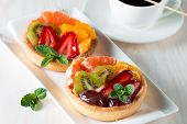 Fresh Fruit And Berry Tart Dessert With Toss Sugar On Wooden Background. Delicious Sweet Cake With R poster