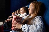 Pretty, Little Girl Holding Popcorn Bucket, Sitting With Friends In Cinema, In Comfortable Chairs. C poster