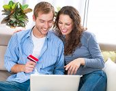 Online Shopping. Happy Smiling Couple Using Credit Card to Internet Shop on-line. Young couple with