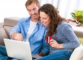 Online Shopping. Happy Smiling Couple Using Credit Card to Internet Shop on-line. Young couple with Laptop Computer and Credit Card buying online. Christmas and New Year Gifts. e-shopping