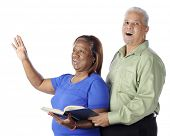 A senior African American couple singing praises together from a hymnal.  On a white background.