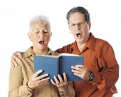 A senior couple happily singing together from the same book.  On a white background.
