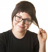 stock photo of fidget  - Young woman playing with hair and grinning - JPG