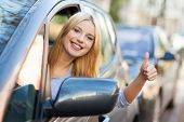 Young woman doing thumps-up in car