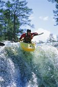 Man Canoeing In Fast Waters