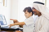 Middle Eastern Man And Child In Home Office Using Laptop