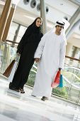 Middle Eastern Couple Walking Through Shopping Mall With Bags