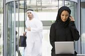 Middle Eastern Business With Woman On Laptop And Cell Phone