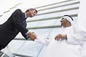 Middle Eastern And Western Business Men Shaking Hands In Front Of Offices
