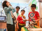 SUBANG JAYA - NOVEMBER 10: A visitor tries to interact with a robot created by unidentified students