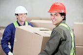 Two foremen lifting cardboard box at warehouse