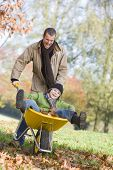 stock photo of tweeny  - Man and young boy outdoors playing with wheelbarrow and smiling  - JPG