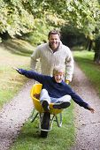 stock photo of tweeny  - Father pushing boy in wheelbarrow - JPG