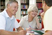 foto of 55-60 years old  - Three people in library writing in notebooks  - JPG