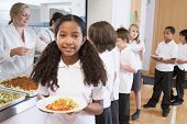 stock photo of school lunch  - Students in cafeteria line with one holding her healthy meal and looking at camera  - JPG