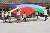 Children Using Parachute To Learn In School Playground
