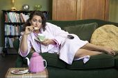 image of housecoat  - Young woman lying on sofa at home eating cookies and drinking tea - JPG