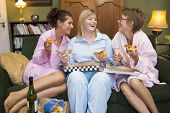 stock photo of housecoat  - Three woman in night clothes sitting at home eating pizza - JPG