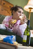 Woman Laid On Sofa With Crisps And Wine