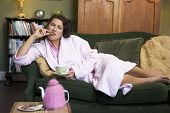 Woman Eating Chocolate And Drinking Tea On Sofa