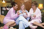 image of housecoat  - Three woman in night clothes sitting at home eating cookies and drinking tea - JPG