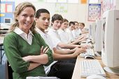 Teacher Helping Teen Pupils Study On School Computers