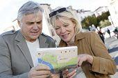 Pareja Senior en ciudad mirando el mapa y tablet