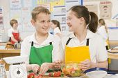 stock photo of tweeny  - Male and female student preparing sliced fruit - JPG
