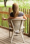 Photo of beautiful girl sitting on veranda and enjoying calm weather, rear view of blond female sit