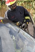stock photo of crew cut  - Firefighter cutting out a windshield after an accident - JPG