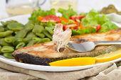 Peixe frito com limão, feijão e salada