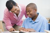 foto of student teacher  - Student in class reading with teacher - JPG