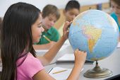 stock photo of tweeny  - Student in class pointing at a globe  - JPG